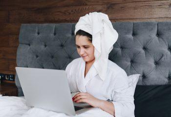 Γυναίκα στο κρεβάτι μπροστά σε φορητό υπολογιστή